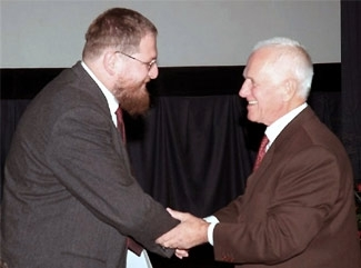 The new director of the Auschwitz-Birkenau Memorial and Museum in Oswiecim, Poland, Piotr Cywinski, left, shakes hands with his predecessor, Jerzy Wroblewski, at a recent retirement party for Wroblewski. (Lidia Foryciarz/Auschwitz-Birkenau Memorial and Museum)