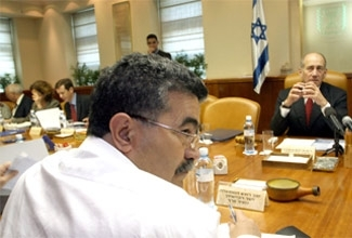 Israeli Defense Minister Amir Peretz, left, sits across from Prime Minister Ehud Olmert in the weekly cabinet meeting at the Prime Minister's office in Jerusalem. (Pool/BPH Images)