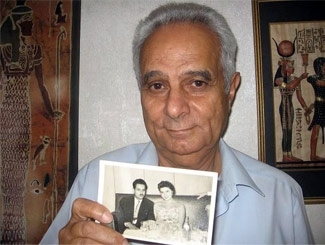 Geoffrey Hanson, at his home in Ramat Gan, Israel, shows a photo of himself and his former fiance at their engagement party in Alexandria, Egypt. (Brenda Gazzar)