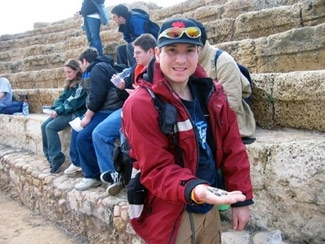 Michael Griner, 22, a participant on the first birthright israel trip for people with Asperger´s syndrome, shows off ancient coins he found on the beach in Caesaria.  (Dina Kraft)