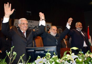 Palestinian Authority President Mahmoud Abbas, left, Prime Minister Ismail Haniyeh, right, and Ahmad Bahar, deputy speaker of Parliament, raise their hands March 17 in Gaza, during the formation of a new unity government.    (PPO/BPH Images)