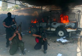 Hamas militants stand close to a burning jeep in the grounds of the a building belonging to the pro-Fatah security forces loyal to P.A. President Mahmoud Abbas after it was taken over in Rafah in the southern Gaza Strip,  June 14, 2007. (Ismail Khateb/BPH Images)