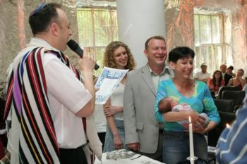 Yuri and Tatyana Podolny with their 19-year-old daughter, Dina, and 10-day-old daughter Eva, at her baby naming during the Sha'arei Shalom dedication ceremony. ()