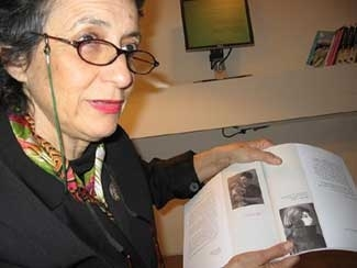 """Yehudit Inbar, curator of """"Spots of Light: To Be a Woman in the Holocaust,"""" displays a catalogue on the Yad Vashem exhibit. (Brenda Gazzar)"""