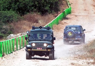 Israeli police patrol a security road alongside where an electrified security fence is being built at the Israeli Arab village of Salem on June 17. (Brian Hendler)
