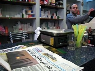 Arab and Hebrew language newspapers lie on the counter in the Malka Cafe in the French Hill neighborhood of Jerusalem on Jan. 21, 2008.   (Brian Hendler)