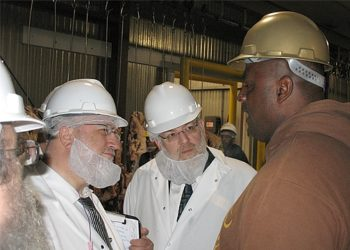 Rabbi Pesach Lerner, center, the executive vice president of the National Council of Young Israel, speaks with a worker at the Agriprocessors plant in Postville, Iowa, on July 31, 2008. (Aaron Troodler)