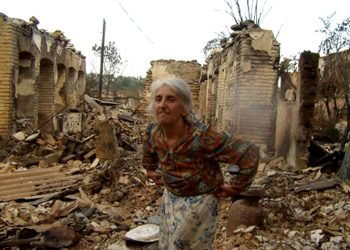 Rosa Jinjikhashvili, the last Jew remaining in the Ossetian capital of Tskhinvali, stands on the ruins of her home. She is living in a summer house next door. (JDC)