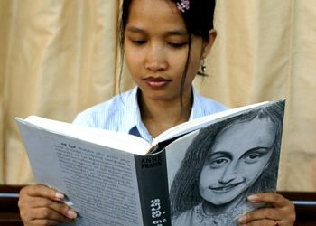 """Sayana Ser reads a copy of the Khmer translation of the """"The Diary of a Young Girl"""" by Anne Frank. (Tibor Krausz)"""