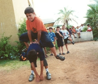 Terror victim Yaniv Amousha, top, plays leap-frog with a friend at summer camp in Hadera. (JDC)