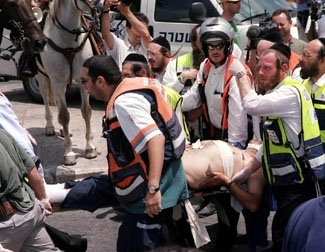 Emergency personnel evacuate a wounded man after a Palestinian gunman opened fire Aug. 4 in Jerusalem, killing two people.  (Avi Ohayon/GPO/BP Images)
