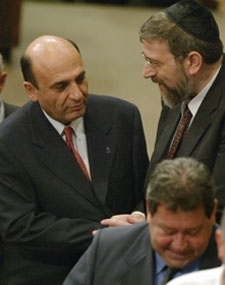 Israel´s new Defense Minister Shaul Mofaz, left, is congratulated by former Deputy Foreign Minister Michael Melchior as the outgoing defense minister, Benjamin Ben-Eliezer, walks away in the Knesset on Nov. 4. (BP Images Pool Photo)
