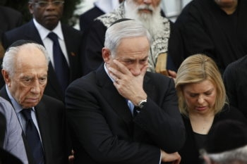 Israeli President Shimon Peres, left, and Prime Minister Benjamin Netanyahu with his wife, Sara, attending the funeral of Netanyahu's father, Benzion, at Givat Shaul cemetery in Jerusalem, April 30, 2012. (Yonatan SIndel/Flash 90)