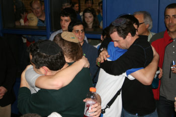 Yair Miller, left, and Ahron Guttman seek comfort from their fathers after losing the championship game, March 3, 2012. (Samantha Steinberg )