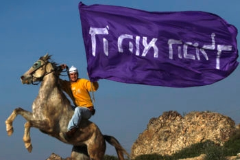 """A settler rides his horse in Havat Gilad while holding a flag that says """"God is the King."""" (Nati Shohat / Flash 90/JTA)"""