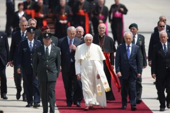 Pope Benedict XVI is flanked by Israeli Prime Minister Benjamin Netanyahu, left, and President Shimon Peres upon his arrival at Ben Gurion International Airport on May 11, 2009. (Flash90 / JTA)
