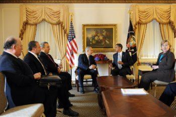 Prime Minister Benjamin Netanyahu, rear left, and President Obama, flanked by Israeli and U.S. officials, speak prior to their Mideast summit on Sept. 22, 2009 in New York City. (Avi Ohayon / GPO / Flash 90 / JTA)