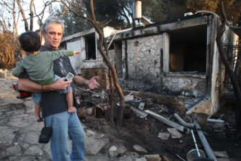 Father and son look at their house in Ein Hod, near Haifa, that was burned down in the fire that ravaged the Carmel Forest, Dec. 5, 2010. (Meir Partush/Flash 90)
