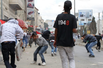 Stone-throwing Palestinians clash with Israeli troops near the Kalandiya checkpoint between the West Bank city of Ramallah and Jerusalem on the 63rd anniversary of the Nakba, May 15, 2011.  (Nati Shohat/Flash 90)