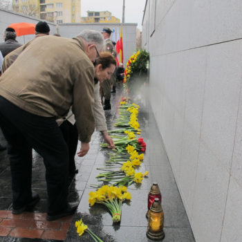 People laying flowers at Umschlagplatz at the Warsaw Ghetto, the monument at the site from which Jews were deported to Treblinka.  (Ruth Ellen Gruber)