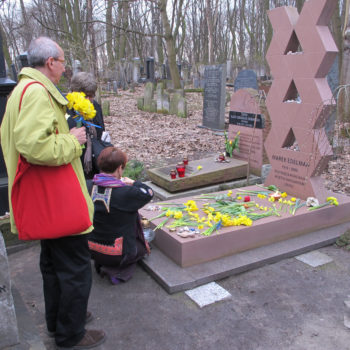 Observers placing daffodils at the grave of Marek Edelman, a commander of the Warsaw Ghetto uprising, in Warsaw's Jewish cemetery.  (Ruth Ellen Gruber)