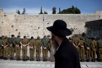 A haredi Orthodox man watching Israeli soldiers at an army ceremony at the Western Wall in Jerusalem, Feb. 22, 2012. (Yonatan Sindel/FLASH90/JTA)