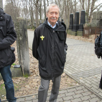 Janusz Onyszkiewicz, a Solidarity activist and former Polish defense minister following the fall of communism,  wearing a paper yellow daffodil in the Warsaw Jewish cemetery.  (Ruth Ellen Gruber)