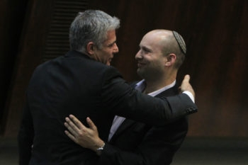 Yesh Atid party leader Yair Lapid hugging Jewish Home party chief Naftali Bennett following Lapid's first speech at the Knesset, Feb. 11, 2013.   (Miriam Alster/Flash90/JTA)