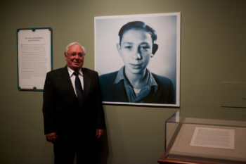 """Holocaust survivor Michael Pupa standing next to his childhood photo in the """"Attachments"""" exhibit at the National Archives in Washington, D.C. (Earl McDonald for the National Archives)"""