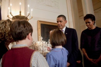 President Obama and First Lady Michelle Obama look on as a child lights the Chanukah candles at a White House reception, Dec. 16, 2009. (White House Photo by Samantha Appleton)