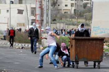 Palestinian protesters throwing stones outside Israel's Ofer military prison in the West Bank, near Ramallah, Feb. 25, 2013.  (Issam Rimawi/Flash90)
