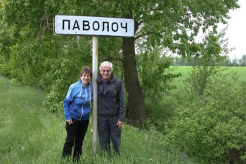 Judy and Lew Priven in 2011 standing next to a sign marking Pavoloch, the village in Ukraine where Lew's father, Julius, was raised.  (Courtesy Lew Priven)