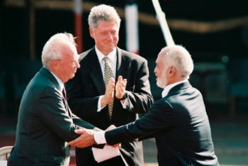 The late Israeli Prime Minister Yitzhak Rabin, left, shaking hands with the late King Hussein of Jordan with U.S. President Bill Clinton in the background during the Israeli-Jordanian peace treaty in Aqaba, Jordan, Oct. 26, 1994.  (Nati Shohat/Flash90)