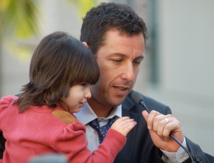 Adam Sandler, holding daughter Sunny, speaking at his star ceremony in Hollywood, Feb. 1, 2011. (Sharon Grapics/Creative Commons)