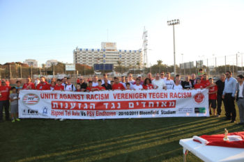 "Israeli and Dutch Soccer fans carrying a sign reading ""fans against racism"" at an event in Tel Aviv, 2011. (FARE Network)"