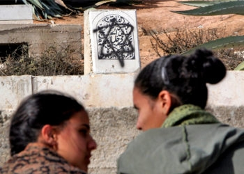 Settlers sit near a Muslim grave in Hebron defaced with a Magen David near the house evicted by Israeli security forces on Dec. 4, 2008. (Brian Hendler)