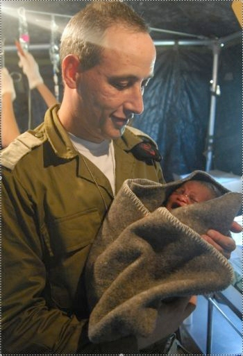 Lt. Col. Dr. Avi Abergel, a gynecologist with the Israeli aid mission to Haiti, holds a premature baby delivered in the IDF field hospital in Haiti on Jan. 17, 2010. (IDF)