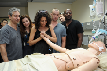 """Lisa Edelstein, a star of the hit television show """"House,"""" jokingly comforts a dummy used in medical simulations at the Sheba Medical Center, an Israeli hospital outside of Tel Aviv alongside fellow cast members and the series creator. (Jorge Novominsky)"""