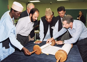 Reuven Firestone, right, co-director of the Center for Muslim-Jewish Engagement, shows the Torah to visiting scholars of Islam. (Marvin Steindler)