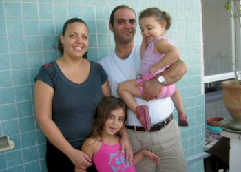 Saher and Fida Abudbai with their two young daughters on the balcony of their apartment in Nazareth Ilit.  (Dina Kraft)
