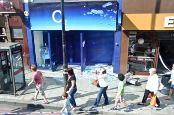 Passers-by glancing at looted stores in a London neighborhood, Aug. 9, 2011. (Creative Commons)
