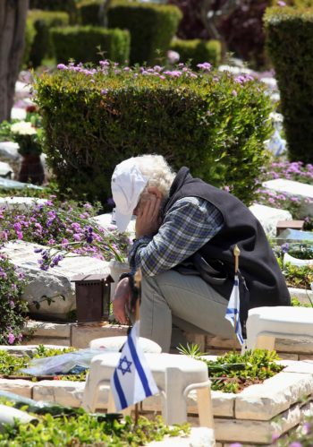 A bereaved Israeli mourning ahead of Israel's Memorial Day at the grave of a fallen soldier at Tel Aviv's Kiryat Shaul military cemetery, April 14, 2013.  (Gideon Markowicz/Flash 90)