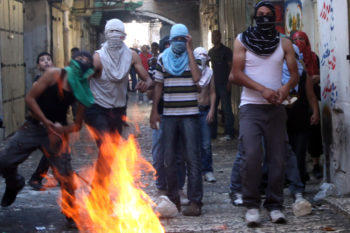 Masked Palestinians throw stones at Israeli policemen in Jerusalem's Old City,  near the Lion Gate,  as part of ongoing violent clashes,  Oct. 25,  2009. (Yossi Zamir / Flash90 / JTA)