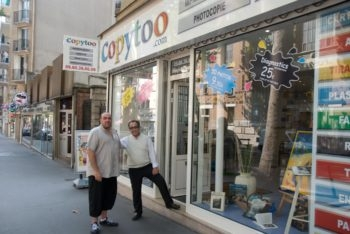 Kamel Amriou, right, and his Jewish partner, who preferred to have his name withheld, outside their printing business in the Belleville neighborhood of Paris. (Ilan Moss)