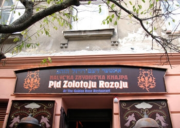 At the Golden Rose cafe in L'viv, Ukraine, patrons are encouraged to don black hats with long, fake earlocks and bargain over the price of the food. (Ruth Ellen Gruber)