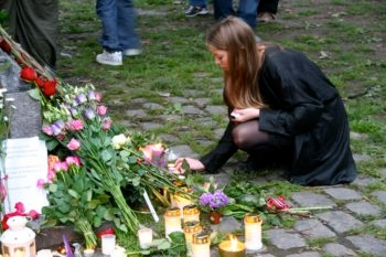 A woman lighting a memorial candle outside the Domkirke Cathedral in Oslo for the July 22 attack victims in Norway, July 25, 2011.  (Alex Weisler)