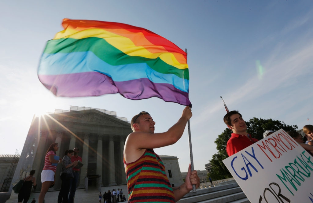Gay rights supporter waving a rainbow flag outside the U.S. Supreme Court building in Washington following its ruling expanding gay rights, June 26, 2013. (Win McNamee/Getty Images)