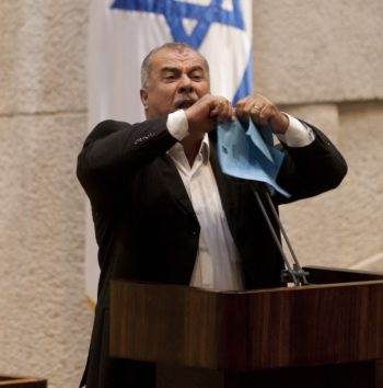 Mohammad Barakeh of the Hadash party tearing the Bedouin settlement bill while speaking in the Knesset, June 24, 2013. (Flash90)