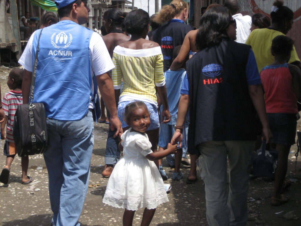 A young girl in Ecuador holding hands with representatives of HIAS, right, and the refugee agency of the United Nations. (Courtesy HIAS)