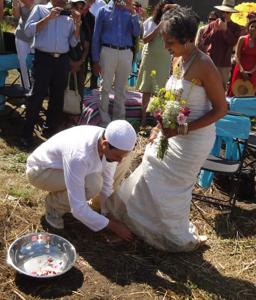 Micha'el BedarShah washes the feet of his bride, Aumatma, during the first wedding ceremony held at Urban Adamah, a Jewish educational farm in Berkeley, Calif., June 30, 2013. (Photos courtesy Micha'el BedarShah)